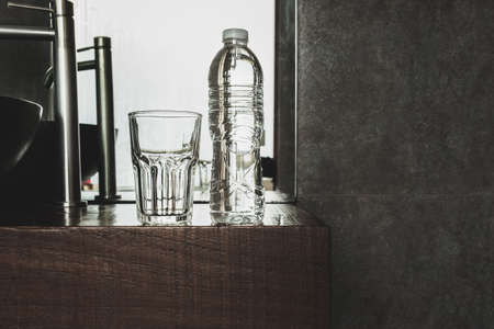 Bottle of mineral water with glasses on wooden top in bathroom.
