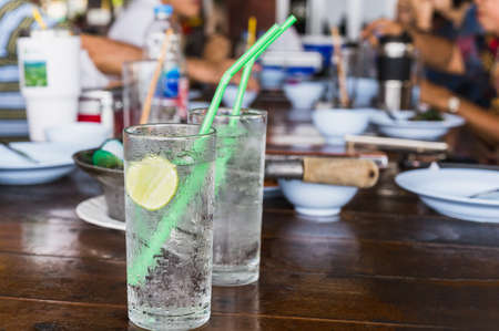 Glass of fresh sparkling water with slice of lime on table.