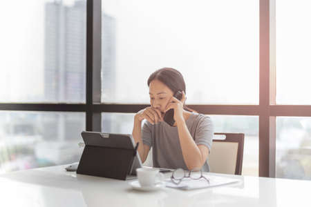 Businesswoman talking on cell phone while working on laptop.