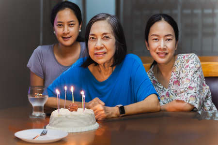 Elderly mother and two adult daughter are celebrating a birthday with birthday cake. Imagens