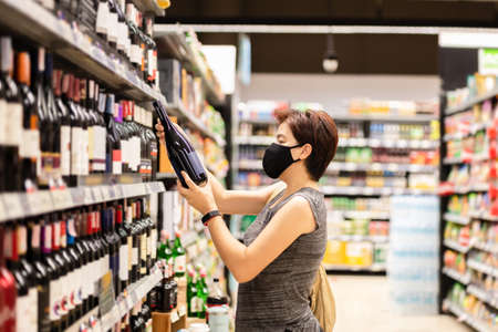 Asian woman in protective mask choosing wine in a wine shop. Stock Photo