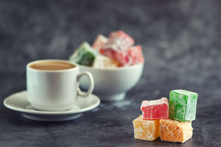 Traditional turkish delight and cup of coffee on gray background.