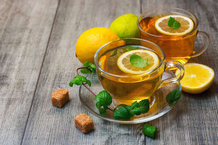 Two Glass tea Cup's with lemon, lime and mint on gray wooden background.