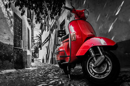 scooters: A red vespa scooter parked on a paved street Stock Photo