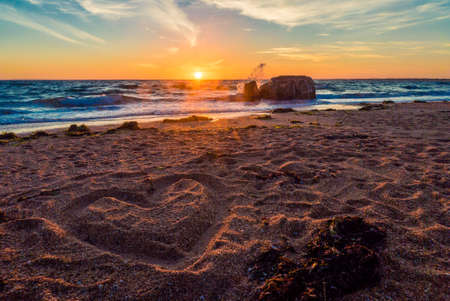 Heart drawn in the sand on a french beach at sunset