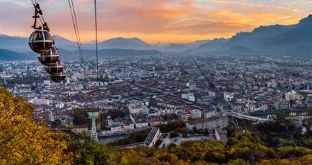 Panorama de Grenoble y sus teleféricos descendiendo en la puesta de sol Foto de archivo - 90545063