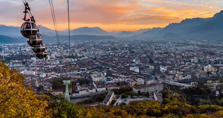 Panorama of Grenoble and its cable cars descending in the sunset