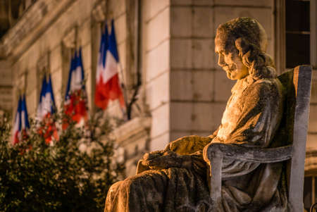 Statue of a man sat on a chair in Avignon at night with french flags in the background