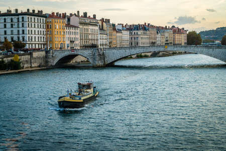 Rhone river and a boat passing in Lyon in France in the summer