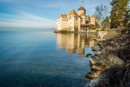 Chillon castle at dawn in the winter with rocks in the foreground Editorial