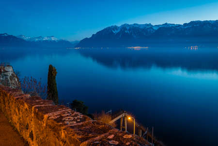 Geneva lake at night with snowy mountains in the background