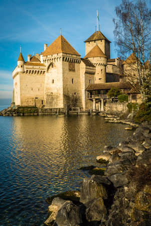 Chillon castle in Switzerland at dawn in the winter with rocks in the foreground