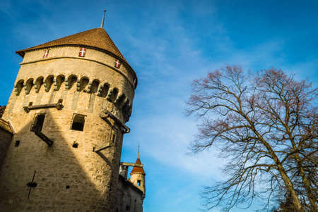 Chillon castle tower lit by the sun at dawn in the winter