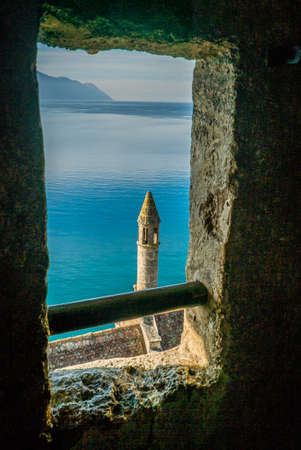 View from Chillon castle windows with a tower and Geneva lake in the background