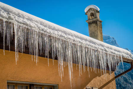 Ice stalactites on a roof brightly shining in the morning sun in winter
