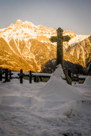 Tumb under the snow with a mountain lit by the sunset in the background Stock Photo