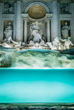 Long-exposure shot of the Trevi fountain in Rome by night with lights on