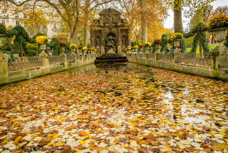 Medici fountain in Jardin du Luxembourg in France, in autumn covered with leaves