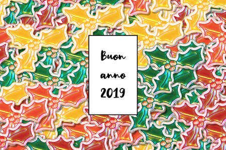 Buon anno 2019 card (Happy New Year in italian) with colored holly leaves as a background Reklamní fotografie