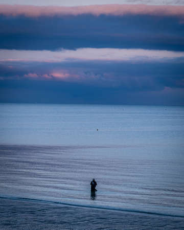 Fisher fishing in Brittany in France at dusk