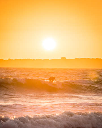 Surf take-off in the sunset in Brittany in France