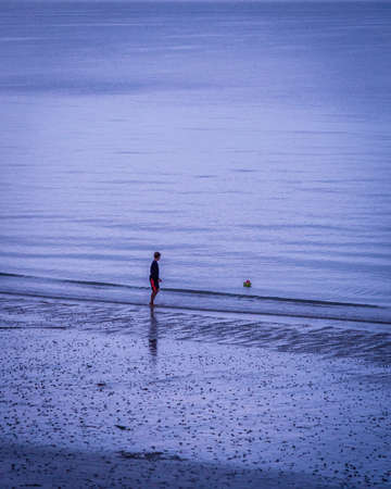 Boy child playing with his boat in the ocean