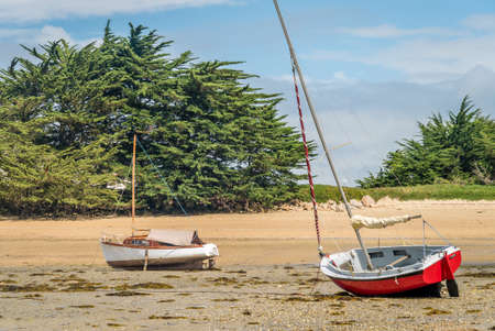 Small sail boats stranded and grounded on the beach in Brittany