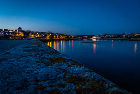 Audiernes town and harbour at night with lights on in Bretagne