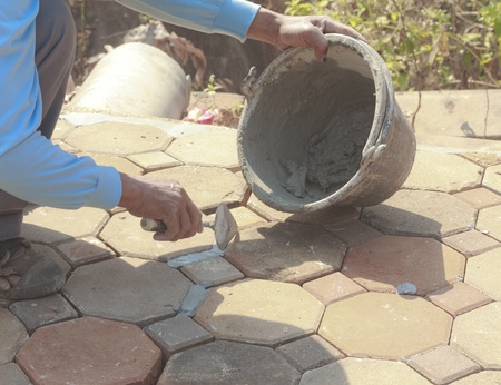 Close-up of men hand holding a trowel, applying mortar