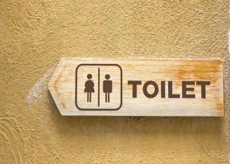 toilet plate sign on orange wall. Stock Photo