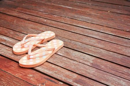 Colorful flip flop sandals on wood background.