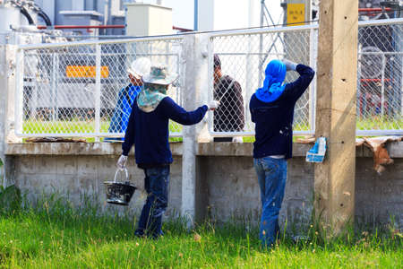 painter rolling new paint on fence of factory. photo