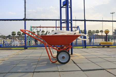 water hose: wheelbarrow with a water hose.