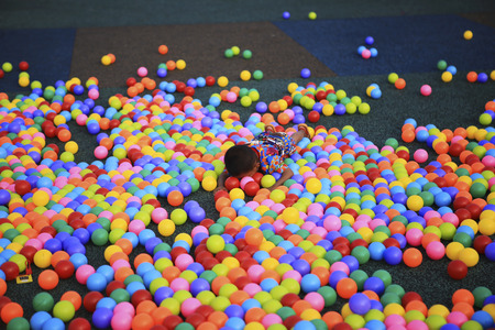 playcentre: boy playing lying in colorful balls park playground.
