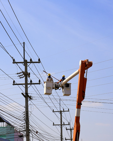 high powered: Khonkean, Thailand- JAN 17:Electrician installing high powered electric cables to cope with the increasing power usage of cities surrounding Khonkean, Thailand on Jan 17,2014.