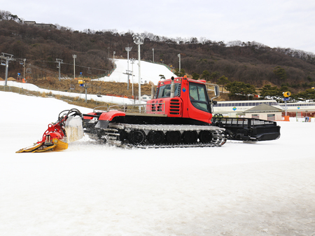 snowcat: Snow-grooming machine on snow hill ready for skiing slope preparations in Korea.