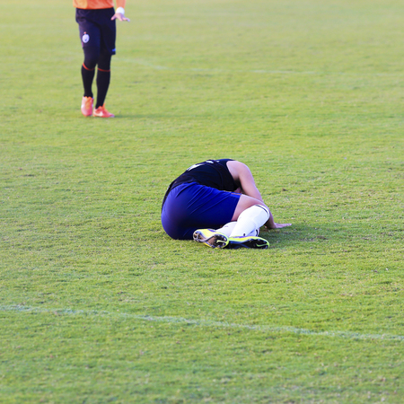 Soccer player lying down on football match. photo