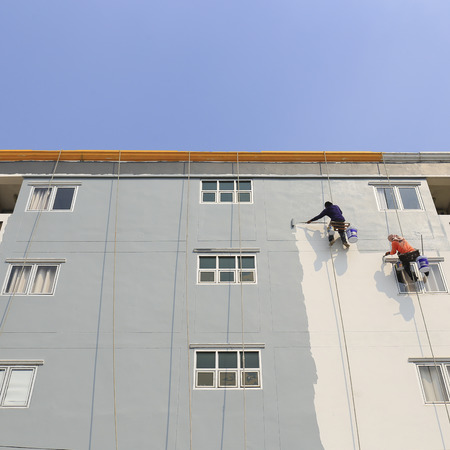 refinish: The painter uses a paint roller outside high building.