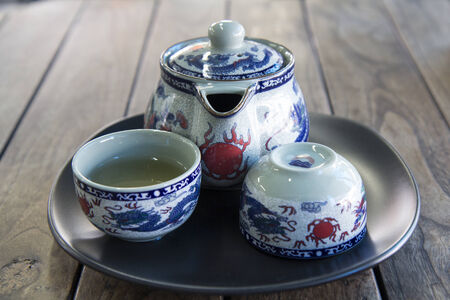 sparce: traditional  teapot and teacups on wooden desk.
