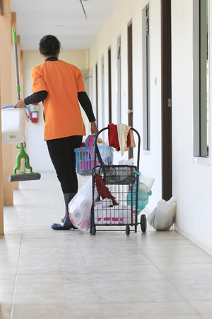 Adult cleaner maid woman with mop and uniform cleaning corridor pass or hall floor of business building.