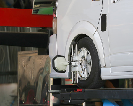 Car wheel fixed with computerized wheel alignment machine clamp. Stock Photo