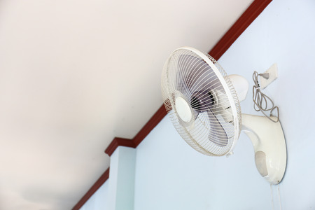 A wall fan with a pull cord switch. Stock Photo