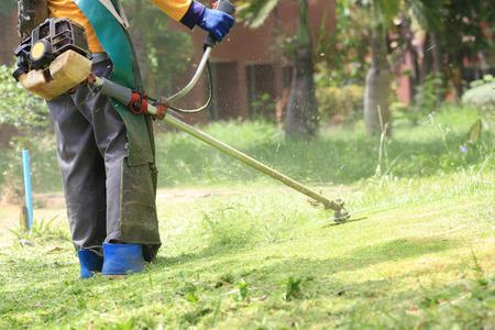 lawn mower worker cutting grass in green field.