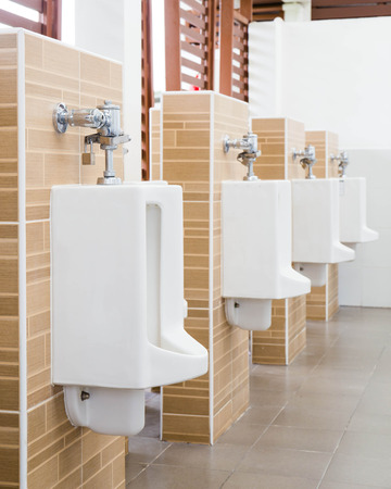 White urinals with ceramic tile on wall