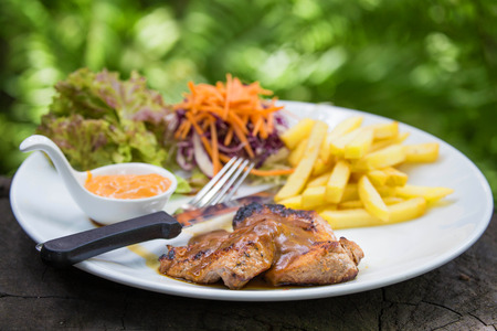 juicy grilled pork chop (neck cut) with greens. photo