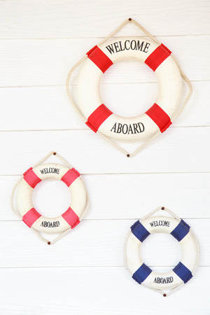 aboard: White Life buoy with welcome aboard on white wall.