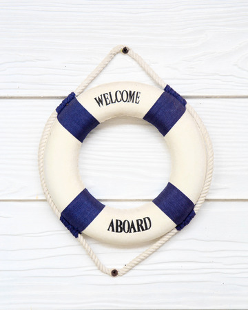 White Life buoy with welcome aboard on white wall.