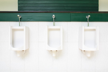 A row of urinals in tiled wall in a public restroom. photo