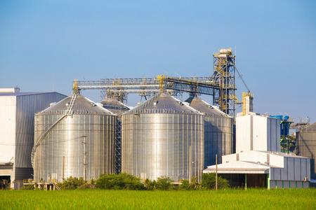 industria petroquimica: Gran blanco planta ubicada con el campo verde. Foto de archivo