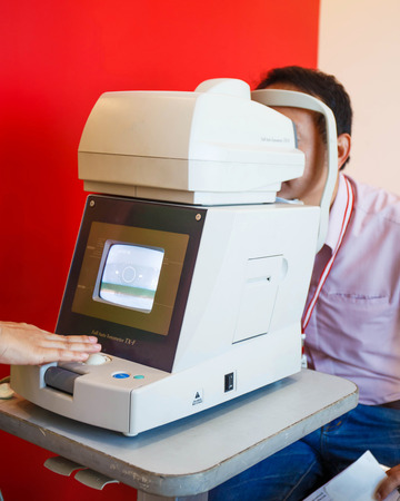 Young Optometrist measuring patients eye pressure with tonometer. photo